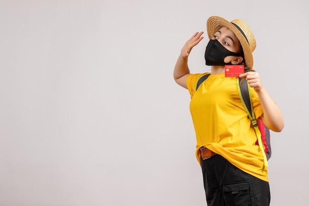 Mulher jovem com uma mochila segurando um cartão e acenando com a mão de frente