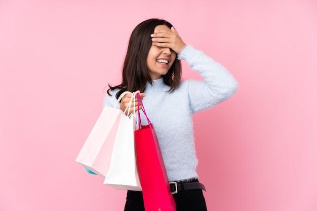 Mulher jovem com uma sacola de compras sobre um rosa isolado sorrindo muito