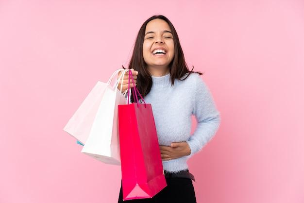 Mulher jovem com uma sacola de compras sobre uma parede rosa isolada e sorrindo muito