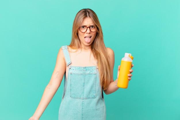 Mulher jovem com uma sensação suave de nojo e irritação e língua de fora