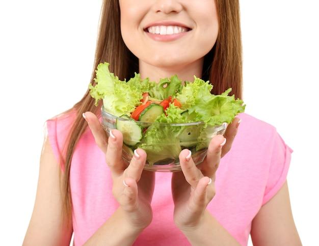 Mulher jovem com uma tigela de vidro de salada de dieta em branco