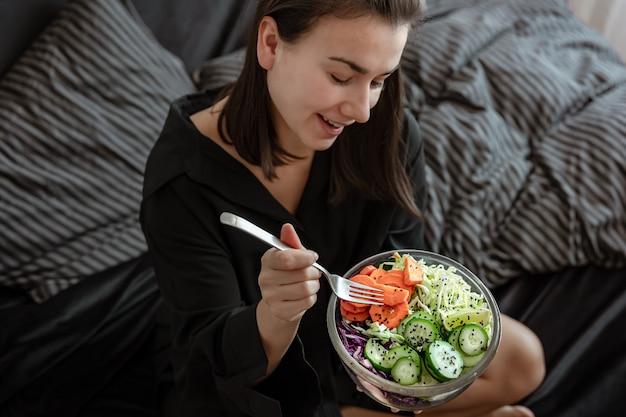 Mulher jovem com uma tigela grande de salada fresca com legumes na cama