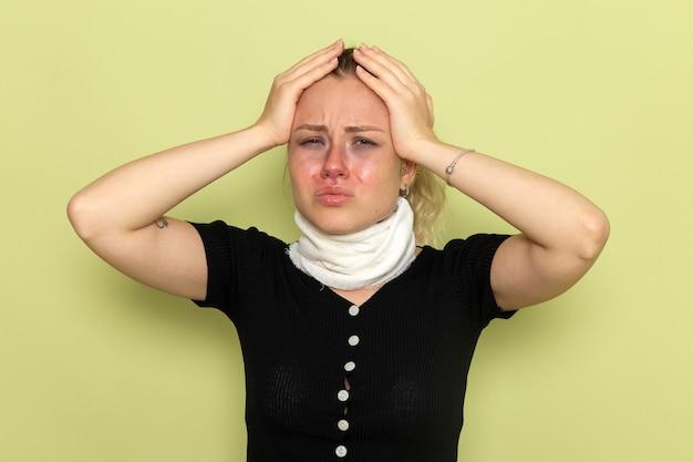 Mulher jovem com uma toalha branca em volta da garganta se sentindo muito mal, com dor de cabeça na parede verde, doença, doença, cor feminina, vista frontal