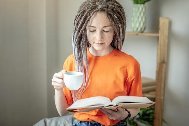 Mulher jovem com uma xícara de café ou chá e roupas brilhantes está sentada e lendo um livro em casa