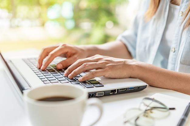Mulher jovem com uma xícara de café usando um laptop