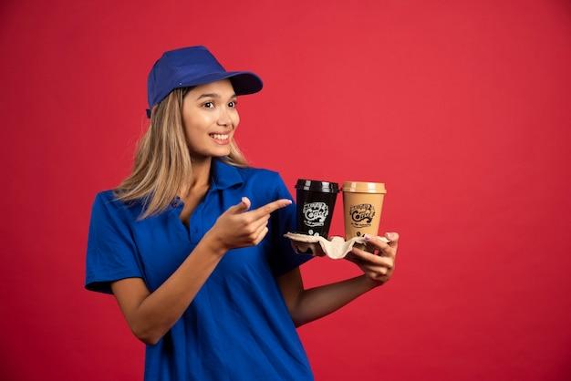 Mulher jovem com uniforme azul, apontando para uma caixa com duas xícaras.