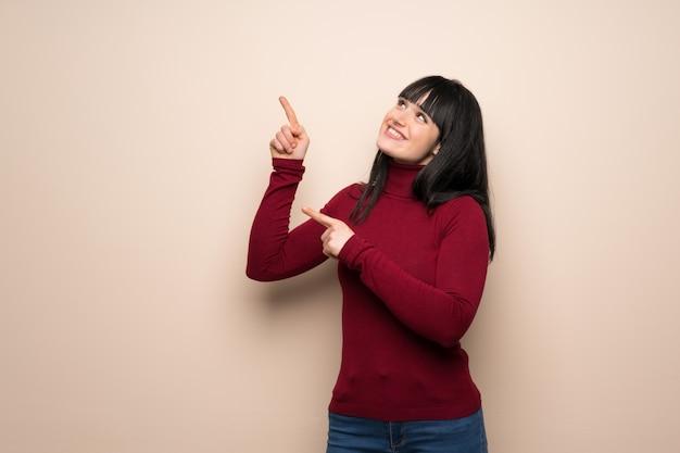 Mulher jovem, com, vermelho, gola alta, apontar, com, a, índice, dedo, e, olhar