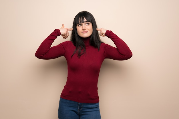 Mulher jovem, com, vermelho, gola alta, cobertura, ambos, orelhas, com, mãos