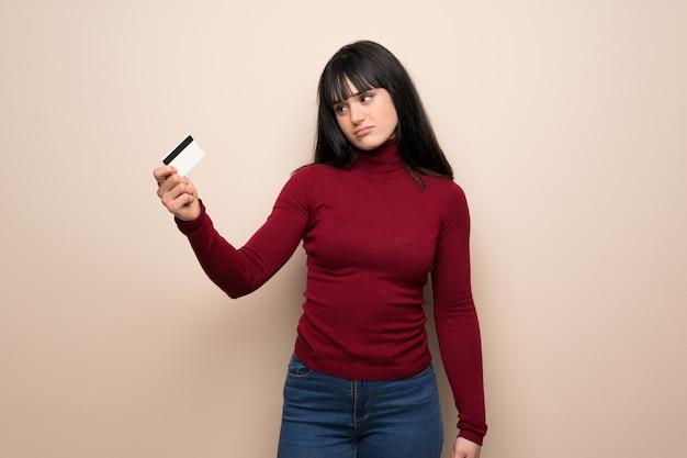 Mulher jovem, com, vermelho, gola alta, levando, um, cartão crédito, sem, dinheiro