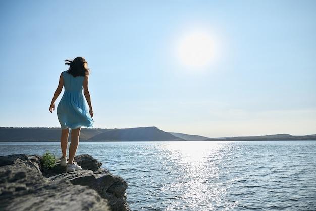 Mulher jovem com vestido azul caminhando à beira do rio