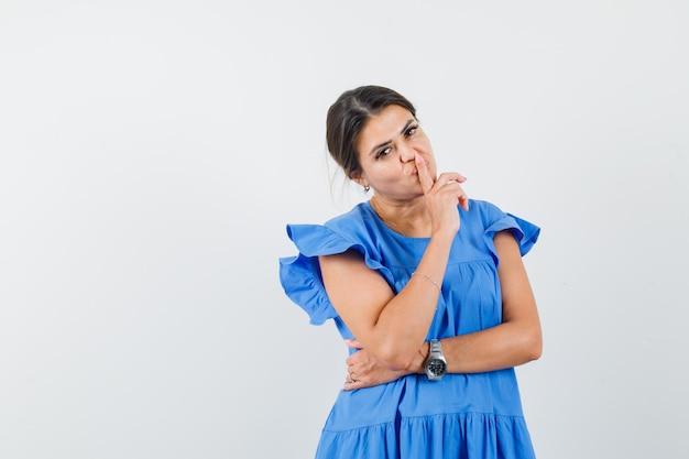 Mulher jovem com vestido azul mostrando gesto de silêncio e olhando com cuidado