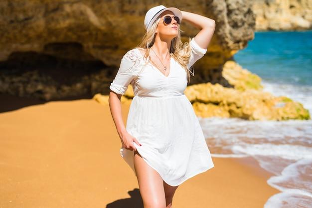 Mulher jovem com vestido branco, chapéu e óculos escuros caminhando na praia rochosa