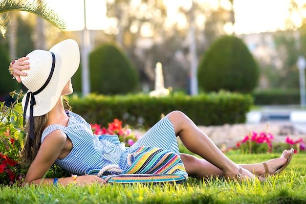 Mulher jovem com vestido de verão azul claro e chapéu de palha amarelo relaxando na grama verde no parque de verão