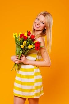 Mulher jovem com vestido de verão e buquê de tulipas
