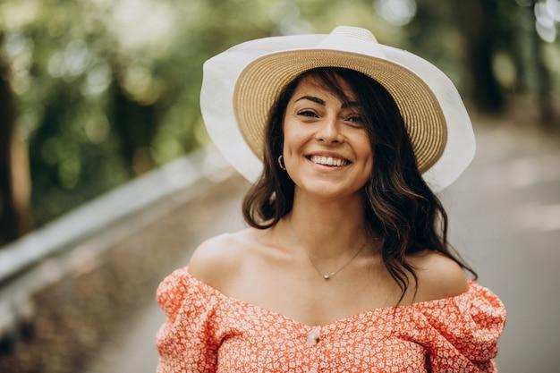 Mulher jovem com vestido e chapéu caminhando no parque