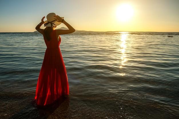 Mulher jovem com vestido longo vermelho e chapéu de palha em pé na água do mar na praia, apreciando a vista do sol nascente no início da manhã de verão