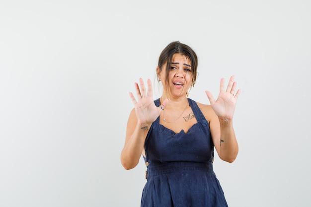 Mulher jovem com vestido mostrando gesto de pare e parecendo irritada