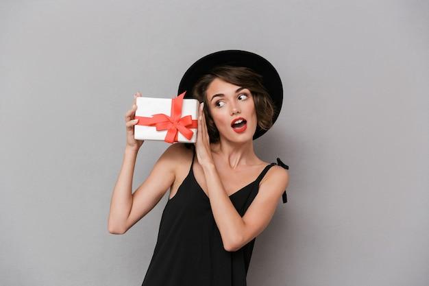Mulher jovem com vestido preto e chapéu segurando uma caixa de presente, isolada sobre uma parede cinza