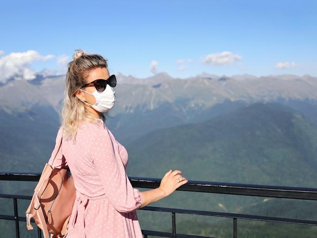Mulher jovem com vestido rosa, óculos escuros e máscara contra o fundo de montanhas