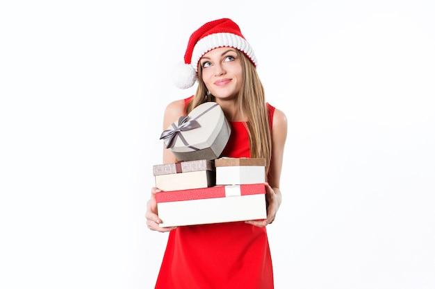 Mulher jovem com vestido vermelho e chapéu de papai noel segurando caixas de presente