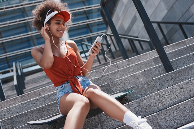 Mulher jovem com viseira estilo livre sentada na rua
