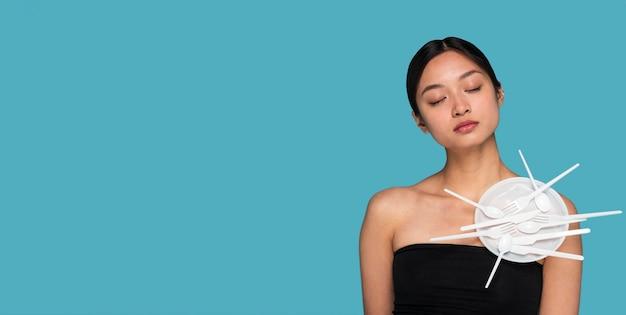 Mulher jovem com vista frontal coberta de talheres de plástico com espaço de cópia