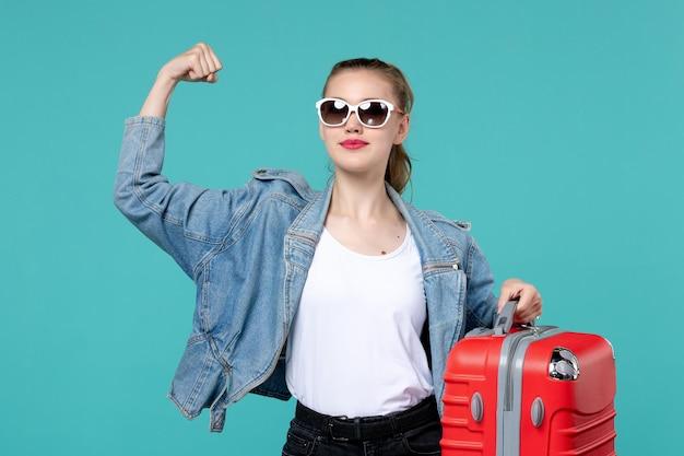 Mulher jovem com vista frontal segurando sua bolsa vermelha e se preparando para a viagem, flexionando-se no espaço azul