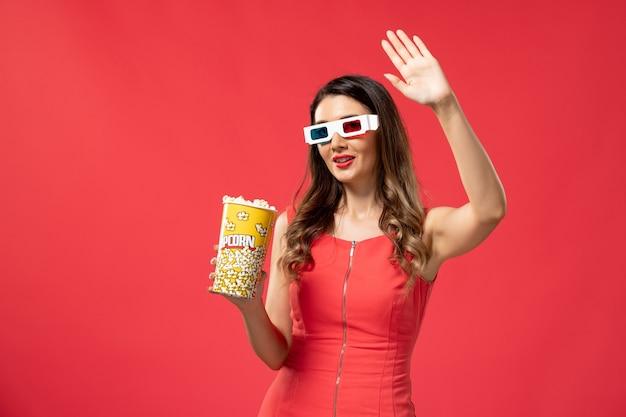 Mulher jovem com vista frontal segurando um pacote de pipoca em óculos de sol d na superfície vermelha