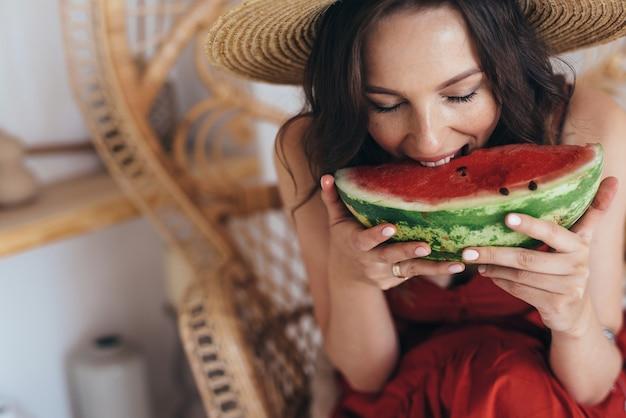 Mulher jovem come um grande pedaço de melancia.