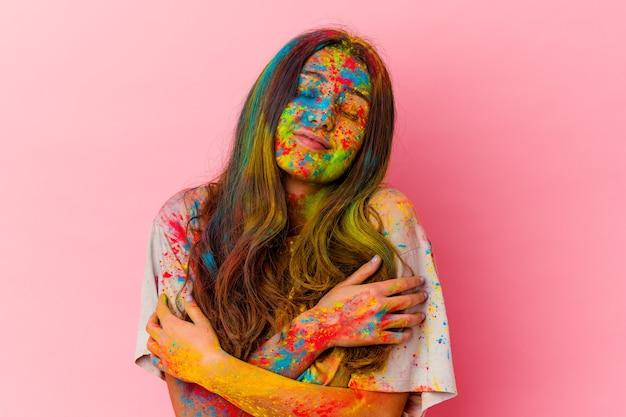 Mulher jovem comemorando o festival sagrado isolado em uma parede branca abraços, sorrindo despreocupada e feliz