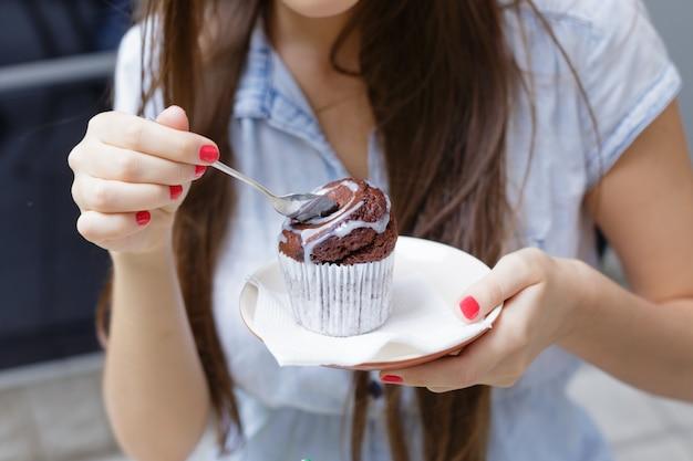 Mulher jovem, comendo bolo, em, café ao ar livre, closeup