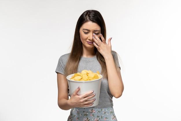 Mulher jovem comendo cips e assistindo filme chorando na superfície branca de frente