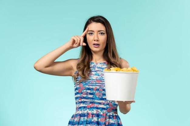 Mulher jovem comendo cips e assistindo filme na superfície azul claro de frente