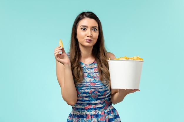 Mulher jovem comendo cips e assistindo filme na superfície azul