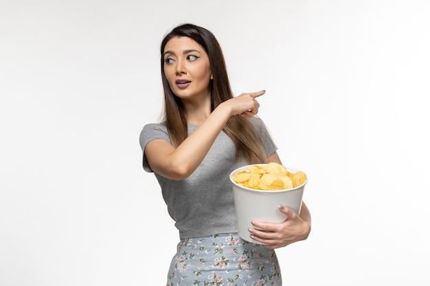 Mulher jovem comendo cips e assistindo filme na superfície branca