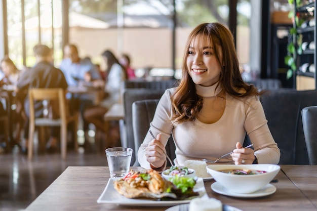 Mulher jovem comendo com comida em restaurante