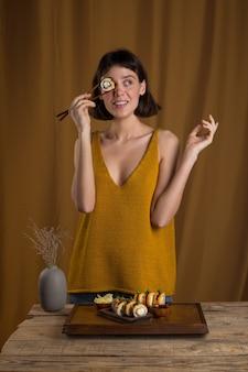 Mulher jovem comendo e saboreando um rolo de sushi fresco usando os pauzinhos