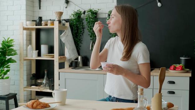 Mulher jovem comendo iogurte na cozinha de casa