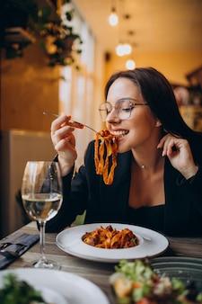 Mulher jovem comendo macarrão em um café