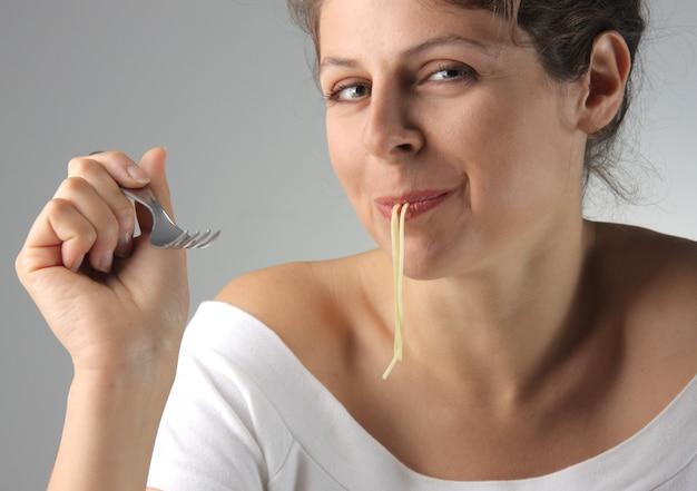 Mulher jovem, comendo macarrão