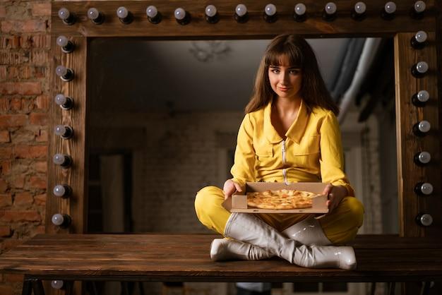 Mulher jovem comendo pizza sentada em uma kombineh amarela