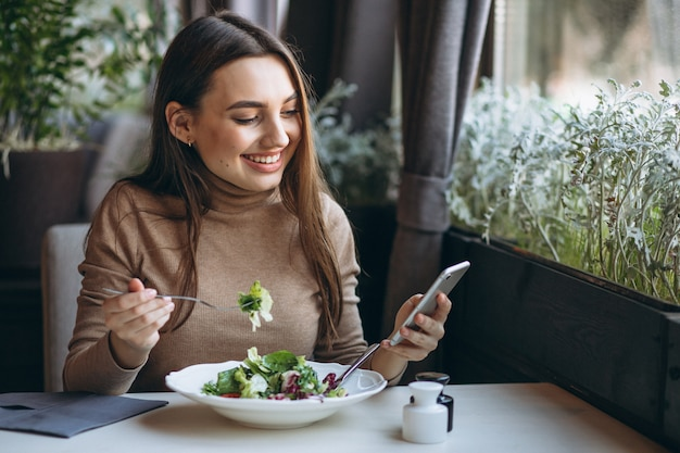 Mulher jovem, comendo salada, em, um, café