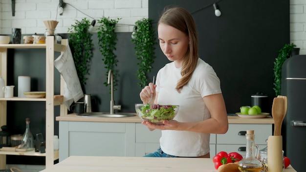 Mulher jovem comendo salada na cozinha de casa