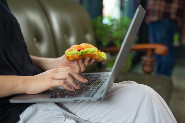 Mulher jovem comendo sanduíches de croissant na sala do escritório
