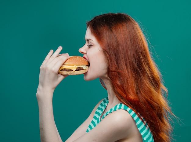Mulher jovem comendo um hambúrguer suculento, um delicioso hambúrguer de fast food