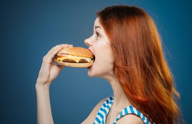 Mulher jovem comendo um hambúrguer suculento