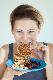 Mulher jovem comendo uma panqueca (waffle). mulher segurando um prato com frutas secas, nozes e waffles. a menina morde um pedaço de waffle. conceito de alimentação saudável