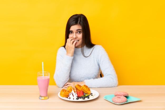 Mulher jovem comendo waffles e milk-shake em uma mesa sobre uma parede amarela isolada, nervosa e com medo