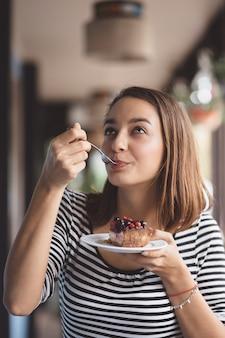 Mulher jovem, comer, cheesecake morango