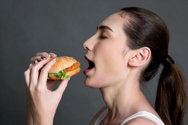 Mulher jovem, comer, hamburger, ligado, cinzento, fundo